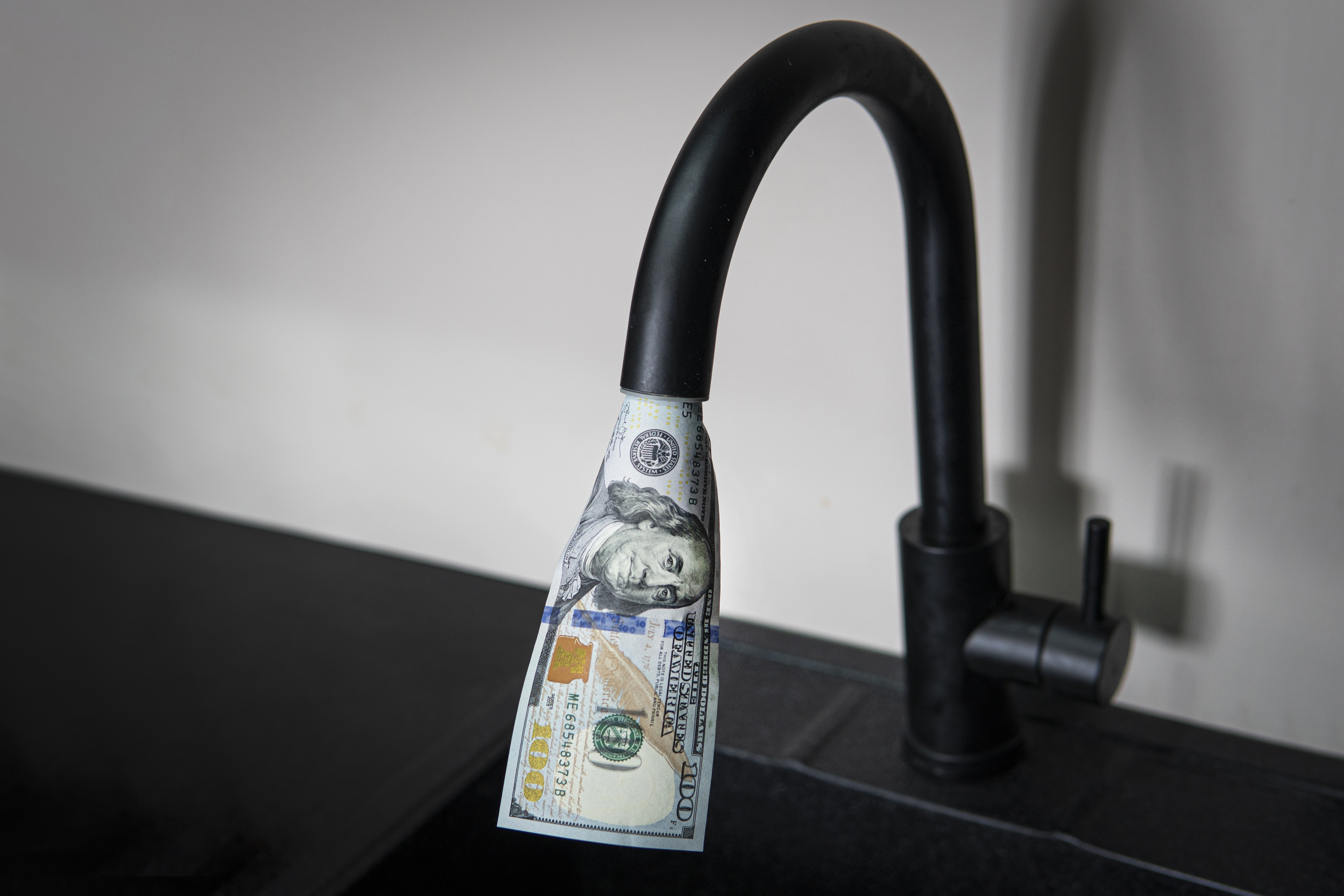 One hundred dollar bill coming out of kitchen faucet.